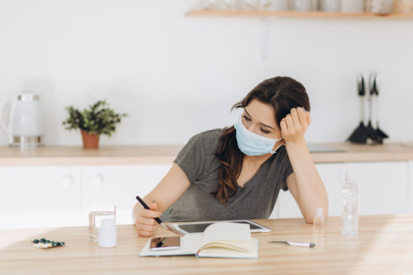Coronavirus. Young business woman working from home wearing prot
